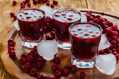 Cranberry drink in glasses. Cold cranberry drink in glasses, cranberries and pieces of ice on wooden background Royalty Free Stock Images