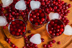Cranberry drink in glasses. Cold cranberry drink in glasses, cranberries and pieces of ice on wooden background Stock Image