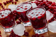 Cranberry drink in glasses. Cold cranberry drink in glasses, cranberries and pieces of ice on wooden background Stock Images