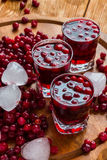 Cranberry drink in glasses. Cold cranberry drink in glasses, cranberries and pieces of ice on wooden background Royalty Free Stock Image