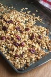 Cranberry Granola. Fresh Cranberry Granola with almonds and dried fruit on metal tray and wooden counter top Stock Images