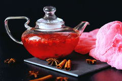 Cranberry herbal hot tea drink in glass teapot with cinnamon and. Star anise spice on black backdrop Stock Photos