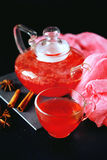 Cranberry herbal hot tea drink in glass teapot with cinnamon and. Star anise spice on black backdrop Royalty Free Stock Image