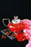 Cranberry herbal hot tea drink in glass teapot with cinnamon and. Star anise spice on black backdrop Stock Image
