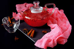 Cranberry herbal hot tea drink in glass teapot with cinnamon and. Star anise spice on black backdrop Royalty Free Stock Images