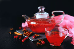 Cranberry herbal hot tea drink in glass teapot with cinnamon and. Star anise spice on black backdrop Stock Photo