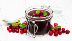 Cranberry jam with fresh fruits. On a old wooden background royalty free stock photo