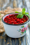 Cranberry jelly and green mint in an enamel mug. Stock Photo