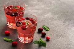Cranberry juice in glasses with mint leaves on a dark table. Selective focus, place for text.  royalty free stock photography