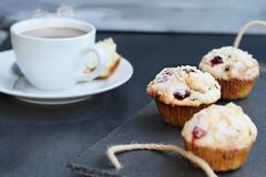 Cranberry Muffins with Fresh Coffee. Cranberry Muffins on a slate serving tray with open muffin with butter and a steaming hot cup of coffee in the background stock image