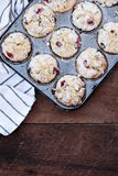 Cranberry Muffins in a Muffin Tin. With kitchen towel over a rustic wood background. Free space for text royalty free stock photo