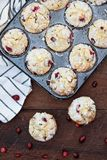 Cranberry Muffins in a Muffin Tin with Fresh Berries. Cranberry Muffins in a muffin tin with kitchen towel over a rustic wood background with scattered fresh royalty free stock photos