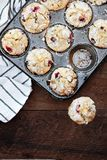 Fresh Cranberry Muffins in a Muffin Tin. Cranberry Muffins in a muffin tin with kitchen towel over a rustic wood background. Free space for text royalty free stock photos
