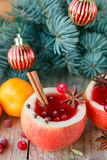 Cranberry mulled wine, apples, tangerines and spices on the table.  Royalty Free Stock Photos
