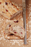 Cranberry pecan oat bread. Loaf and slices of cranberry pecan oatmeal bread with a knife, wood cutting board and scattered oats Stock Photo