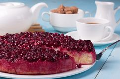 Cranberry pudding on blue wooden table with cup of. Cranberry rice pudding on blue wooden table with cup of tea, sugar bowl full of brown sugar, tea pot and milk Royalty Free Stock Photography
