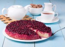 Cranberry pudding on blue wooden table with cup of tea Royalty Free Stock Photography