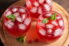 Cranberry refreshment cocktail with mint leaves and ice cubes on the wooden cutting board. Three glasses with cold summer berry drink Royalty Free Stock Image