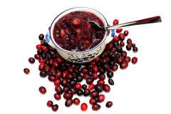 Cranberry Sauce. Fresh cranberries on a white background with a bowl of cranberry sauce on top of the berries Stock Image