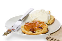 Cranberry Scone. Homemade cranberry scone sliced in two with marmalade and fresh cream against a white background Stock Photography