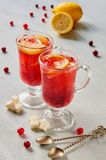Cranberry tea or hot winter sangria with fresh lemon slices in glasses on the gray concrete kitchen background. Side view royalty free stock image