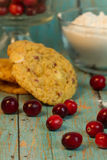 Cranberry White Chocolate Chip Cookies. On a wooden plank board with wholesome whole cranberries in the background royalty free stock photo