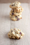 Cranberry White Chocolate Oatmeal Cookies. Oatmeal cookies with cranberries and white chocolate chunks on a wooden counter top Stock Image