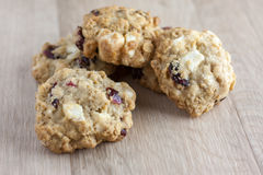 Cranberry White Chocolate Oatmeal Cookies. Oatmeal cookies with cranberries and white chocolate chunks on a wooden counter top Royalty Free Stock Images