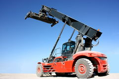 Crane. A red,dusty container crane vehicle isolated on blue sky background royalty free stock photos