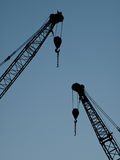 Crane. Two construction crane silhouette on blue sky Royalty Free Stock Photography