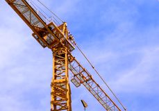 The Crane. Yellow crane against a blue sky Royalty Free Stock Images