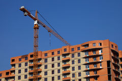 Crane. General plan for the tower crane being built next to the multi-storey house on blue sky background Stock Image