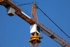 Crane. Close-up of a tower crane cab on blue sky background Stock Photos