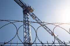 Crane. To the construction area protected by wire mesh Royalty Free Stock Image