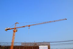 Crane. Orange hoisting crane on site with sky background stock photo