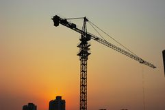 Crane. The large crane beside the building with the sunsets background Royalty Free Stock Photography