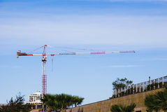 Crane. Big machine for raising heavy objects against the blue sky background Stock Photos