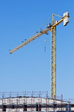 Crane. Yellow crane in a contruction site abd a building with scaffolding Royalty Free Stock Photo