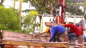 Crane activity at construction site, workers carry stock video footage