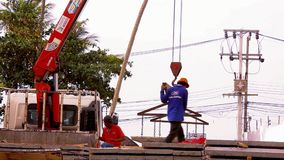 Crane activity at construction site, workers carry stock video