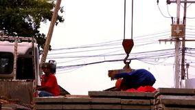 Crane activity at construction site, workers carry stock footage