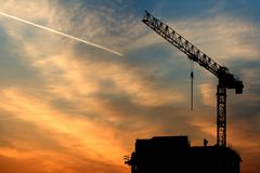 Crane, airplane and sunrise. Beautiful sky at sunrise in city. Building under construction and worker at top of the building. And airplane at sky Royalty Free Stock Images