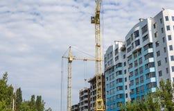 Crane And Building Under Construction Against Blue Cloudy Sky. Stock Photos