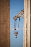 Crane appearing between two marble Parthenon columns Royalty Free Stock Images