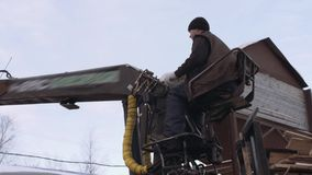 Crane arm loader unloads lumber scraps from heavy truck at sawmill factory. Cold cloudy winter day stock video footage