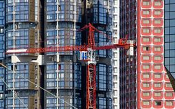 Crane on the background of modernity. Contrasts horizontality and verticality Royalty Free Stock Photo
