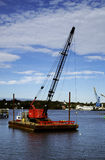 Crane on a Barge. A large crane on a barge in the water royalty free stock photo