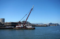 Crane on barge does Pier repair work with Coit Tower Stock Photo