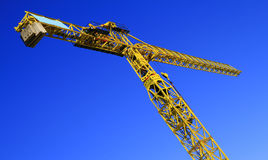 Crane on blue sky. Tall yellow industrial crane on a seamless blue sky Royalty Free Stock Photography