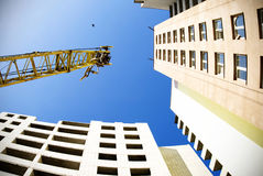 Crane on blue sky with bird Royalty Free Stock Image